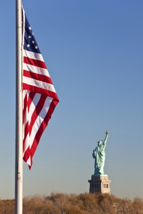@Glowimages: The Statue of Liberty, New York City, United States of America with the Stars and Stripes flag in the foreground