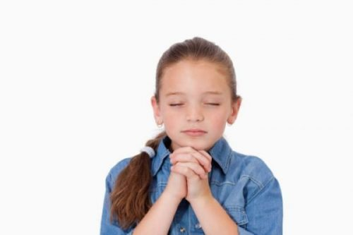 @Glowimages: Little girl praying. Little girl praying against a white background